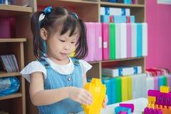 演奏塑料块的学龄前年龄女孩 免版税库存照片