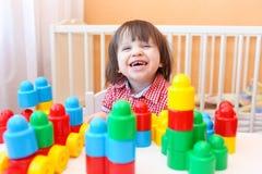 演奏塑料块的滑稽的微笑的小男孩 图库摄影