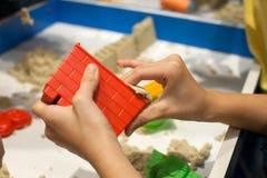 演奏塑料模子的孩子戏弄与在沙盒的沙子 免版税库存图片