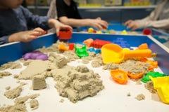 演奏塑料模子的孩子戏弄与在沙盒的沙子 库存图片