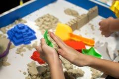 演奏塑料模子的孩子戏弄与在沙盒的沙子 免版税库存照片