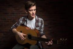 演奏声学吉他和唱歌的英俊的被集中的年轻人 免版税库存图片