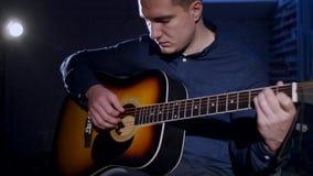 演奏声学吉他黑暗背景的年轻人 免版税库存图片