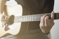 演奏声学吉他特写镜头与阳光的人绳子Em 免版税库存照片
