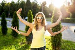 演奏夏天的两个姐妹停放,获得乐趣,做从手标志的瑜伽,户外,玻璃放松 免版税库存图片