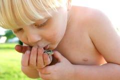 演奏外部亲吻的青蛙的肮脏的小孩 免版税库存图片