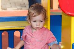 演奏外部操场,奇怪孩子的黑眼睛的孩子在公园,愉快的童年 库存图片