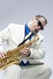 演奏女低音萨克斯管和Weari的白种人成熟男性音乐家 库存照片