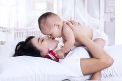 演奏她的婴孩的年轻母亲 库存图片