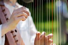 演奏妇女的特写镜头竖琴 免版税库存照片
