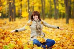 演奏妇女年轻人的秋叶 免版税库存图片