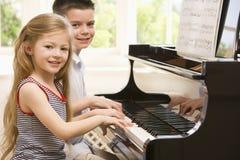 演奏姐妹的兄弟钢琴 库存图片