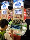 演奏娱乐游戏机器的未认出的孩子 图库摄影
