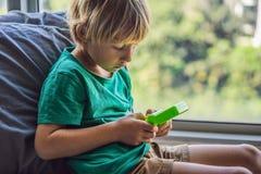 演奏守旧派便携式的比赛控制台,有单色显示的电子减速火箭的口袋玩具的年轻男孩 免版税库存照片