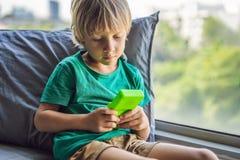 演奏守旧派便携式的比赛控制台,有单色显示的电子减速火箭的口袋玩具的年轻男孩 免版税库存图片