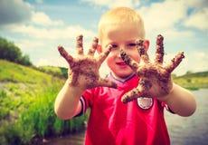 演奏室外陈列肮脏的泥泞的手的孩子 免版税库存图片