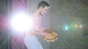 演奏小手鼓的一个人在一间明亮的屋子 股票录像