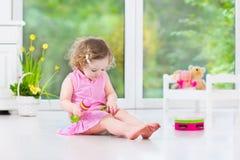 演奏小手鼓的逗人喜爱的卷曲小孩女孩在一个晴朗的绝尘室 库存照片