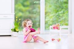 演奏小手鼓的滑稽的小孩女孩在绝尘室 库存照片