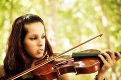 演奏小提琴年轻人的女孩 库存图片