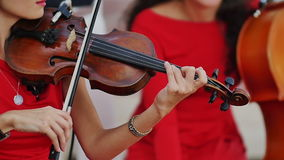 演奏小提琴关闭的红色礼服音乐家的妇女