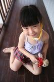 演奏小狗听诊器玩具的女孩 免版税库存图片