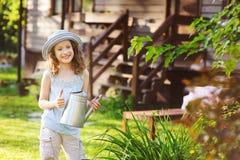 演奏小花匠和帮助的帽子的愉快的孩子女孩浇灌花 免版税图库摄影