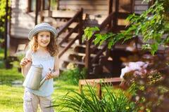 演奏小花匠和帮助的帽子的愉快的孩子女孩浇灌花 免版税库存照片