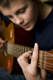 演奏少年的吉他 免版税库存照片
