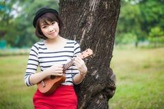 演奏尤克里里琴的女孩在室外的公园 免版税库存照片