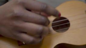 演奏尤克里里琴的女性手接近的看法  弹奏经典木尤克里里琴乐器的非裔美国人的妇女 股票视频