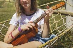 演奏尤克里里琴-在吊床的夏威夷吉他的美丽的女孩 图库摄影