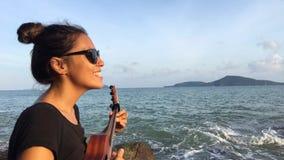 演奏尤克里里琴和唱歌在海滩的逗人喜爱的白种人女孩 HD 花房子湖普吉岛泰国 股票视频