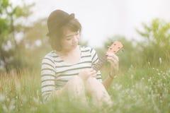 演奏尤克里里琴的亚洲妇女在公园 免版税库存照片
