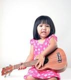 演奏尤克里里琴的小女孩 图库摄影