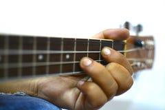 演奏尤克里里琴的手 免版税库存照片