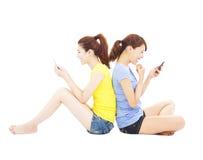 演奏巧妙的电话的两个愉快的俏丽的女孩 免版税库存图片