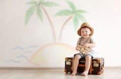 演奏带着手提箱的可爱的小孩旅客 图库摄影