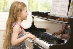 演奏年轻人的女孩钢琴 库存照片