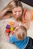演奏年轻人的男婴母亲 免版税库存图片