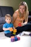 演奏年轻人的男婴母亲 免版税库存照片