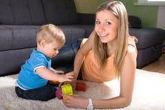 演奏年轻人的男婴母亲 库存照片