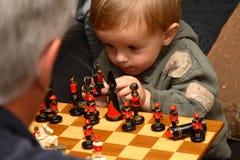 演奏年轻人的男孩棋 免版税库存照片