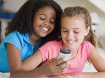 演奏年轻人的移动电话女孩 库存图片