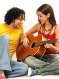 演奏年轻人的cuople吉他 免版税库存图片