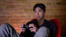 演奏录影cames的年轻韩国男人特写镜头画象使用坐在辎重袋的控制台户内 股票视频