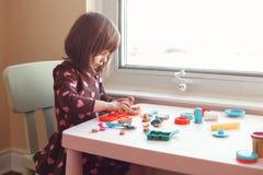 演奏彩色塑泥playdough的白白种人学龄前儿童女孩户内在家 库存照片