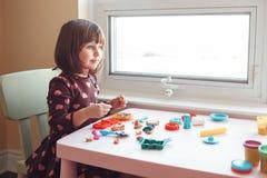 演奏彩色塑泥playdough的白白种人学龄前儿童女孩户内在家 免版税库存照片