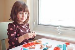 演奏彩色塑泥playdough的白白种人学龄前儿童女孩户内在家 免版税库存图片