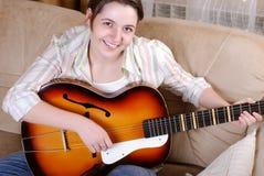 演奏微笑的女孩吉他少年 图库摄影